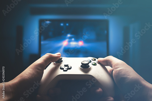 Video gaming console. Man playing car racing Fototapet
