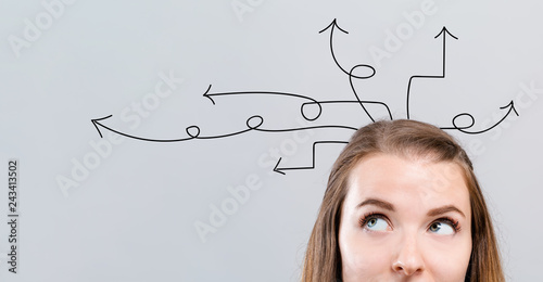 Idea arrows with young woman looking upwards on a gray background