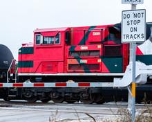 Diesel Engine Pulling Train At Street Crossing.