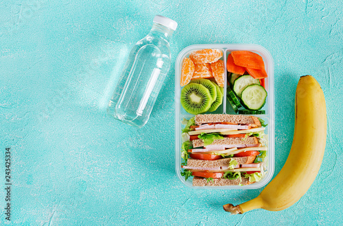 Foto op Plexiglas Assortiment School lunch box with sandwich, vegetables, water, and fruits on table. Healthy eating habits concept. Flat lay. Top view
