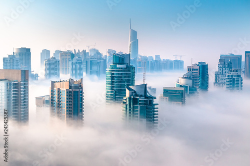 Aerial view of skyscrapers in the clouds. Morning winter fog over Dubai Marina. City above the clouds - 243425387