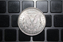 United States Of America Coin One Silver Dollar On The Keyboard. US Morgan Silver Dollar Coin 1921
