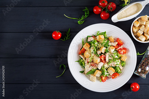 Healthy grilled chicken Caesar salad with tomatoes, cheese and croutons. North American cuisine. Top view