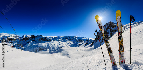 Poster Winter sports Ski in winter season, mountains and ski touring equipments on the top in sunny day in France, Alps above the clouds.