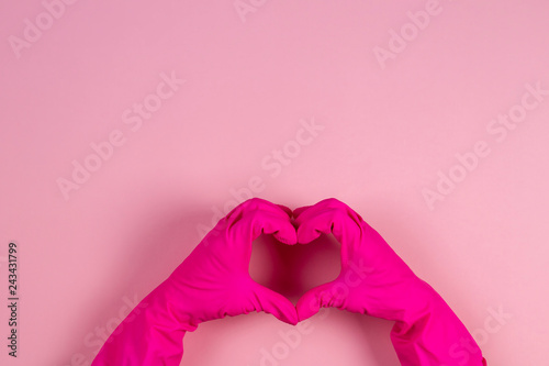 Vászonkép Top view of female hands in pink rubber gloves making heart shape with fingers o