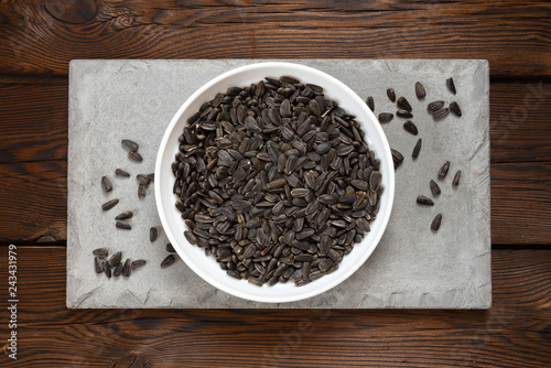 Fotografie, Obraz  sunflower seeds in a white plate on a concrete tile on a  wooden background