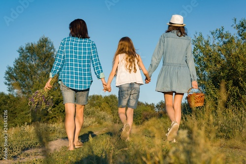 Fotografia, Obraz  Happy mother and two daughters holding hands walking along rural country road with wildflowers, basket of berries