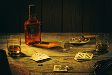 Table With Playing Cards, Whiskey, Cigar And Weapons