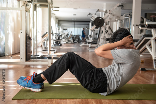 Fotografía  Full length of young   athletic  man in sportswear doing push-up  muscular exercising on green mat in fitness gym