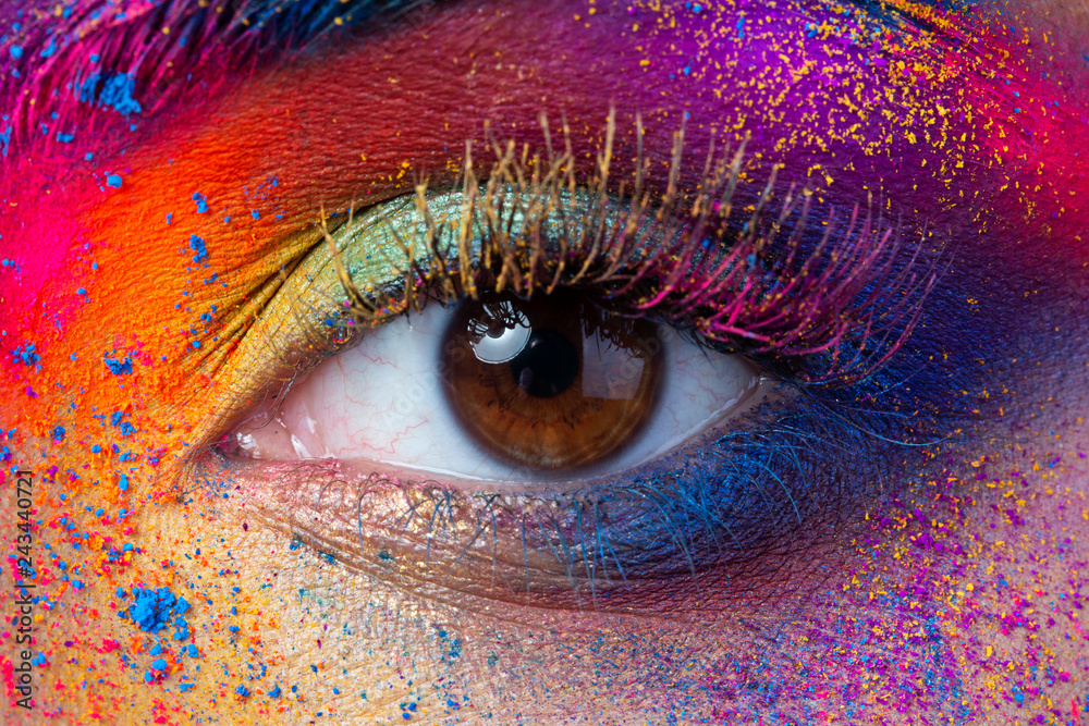 Fototapeta Close up view of female eye with bright multicolored fashion makeup. Holi indian color festival inspired. Studio macro shot