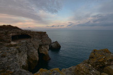 Twilight After Sunset. Cliffs With Caves Rise Above The Calm See. The Black Sea Coast Near Tyulenovo, Bulgaria