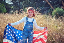 Boy In Nature Holding An Ameri...