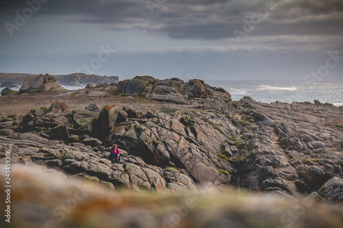 Fotografía  young woman sitting on rocks  of the island of Yeu
