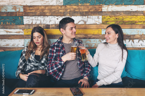 Photographie Man toasting and drinking beer with cheerful woman ignoring jealous girl sitting