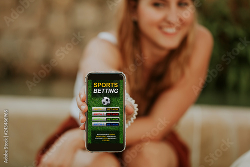 Fotografía  Sports betting website in a mobile phone and woman holding the device in the hand