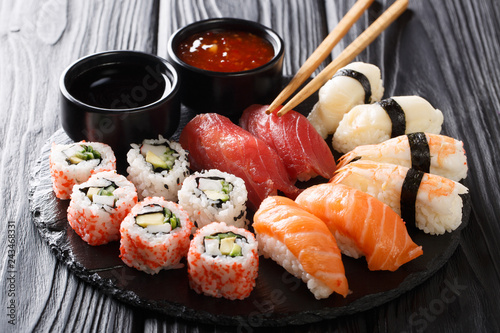 Uramaki and nigiri sushi served in black plate closeup. horizontal