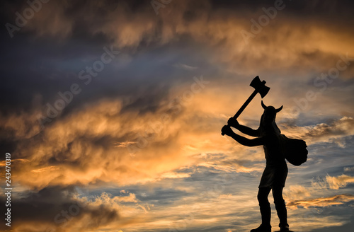 Photo  Dark silhouette of a Viking holding a double-sided axe against orange-blue storm