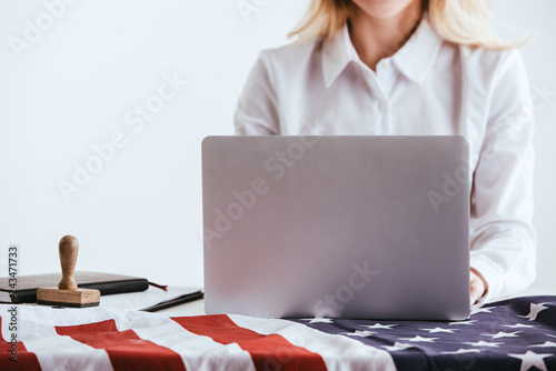 cropped view of woman using laptop near american flag isolated on white