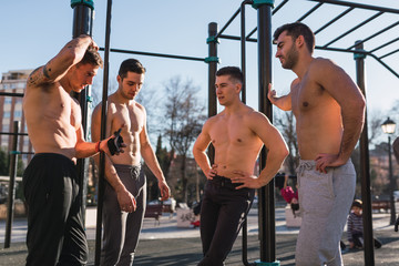 Young sportive men standing near pull up bars in outdoor gym