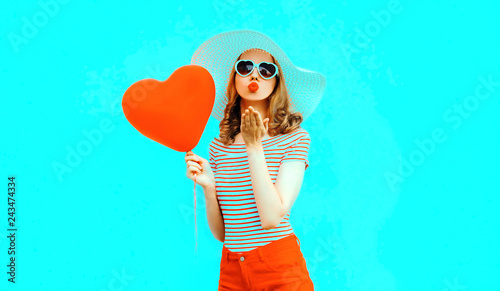 Fotografie, Obraz  Beautiful young woman with red heart shaped balloons sending sweet air kiss on c