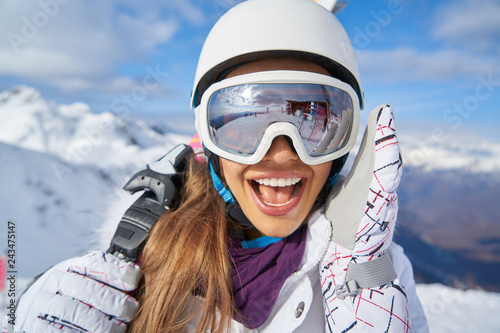 plakat Portrait of beautiful woman with ski and ski suit in winter mountain.