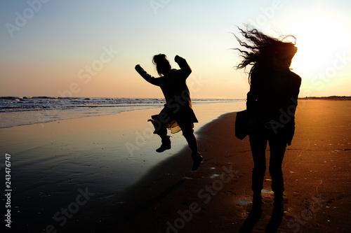 Photo  夕焼けの海辺ではしゃぐ女友達