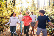Small Group Of Runners Dressed In Sportswear Talking And Walking Through Woods In Autumn.