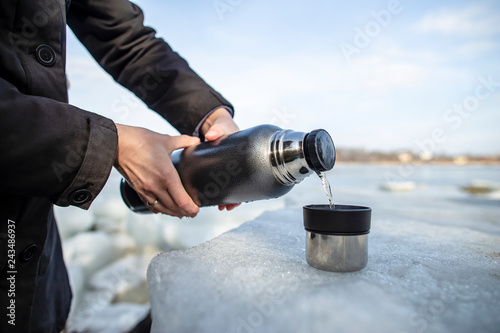 person pours hot tea from a thermos into a cup which stands on an ice floe on the river bank in the spring sunny day