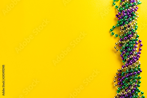 Fotografía  Mardi gras carnival concept - beads on yellow background, top view