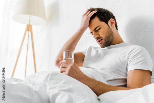 Fototapeta tired man with headache holding glass of water in bed in the morning