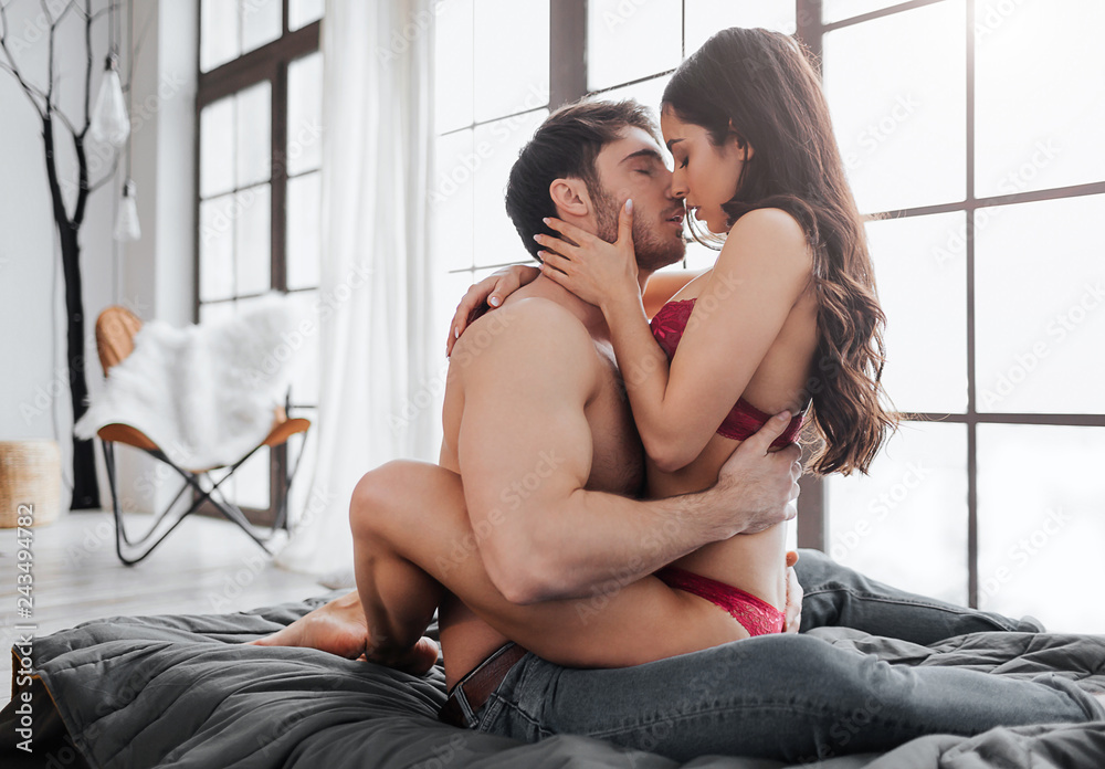 Fototapety, obrazy: Hot passionate couple sitting on bed in room and kissing. She sit on him and embrace with legs. Guy touch her naked back and bring forward.
