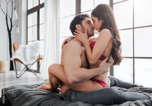 Vászonkép Hot passionate couple sitting on bed in room and kissing