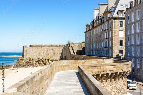 Fotomural View over the rampart walk of the old town of Saint-Malo in Brittany, France, above the Môle beach on a sunny day, with the bastion of Holland in the background