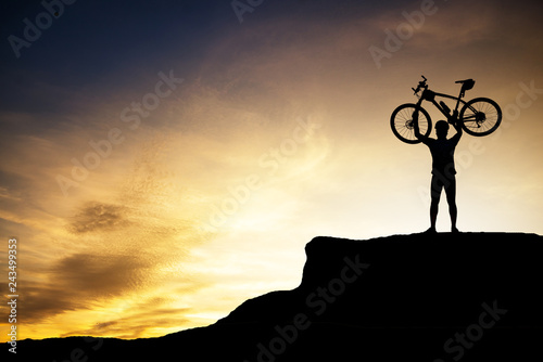 Fototapeta Silhouette of human holding mountain bike on the top of the mountain with beautiful sunset sky