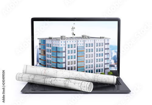 Photo laptop, on which is located a multi-storey building and rolls with drawings