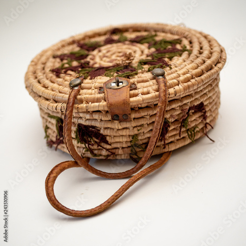 Fotografie, Obraz  Straw round straw hat on  basket with leather handles