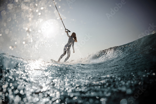 Blonde girl standing on the wakeboard holding a rope