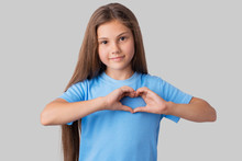 Adorable Small Girl In Blue T-shirt Making A Heart Gesture With Her Fingers With A Happy Sincere Smile. Studio Portrait Of A Little Beautiful Girl Showing Heart With Her Hands
