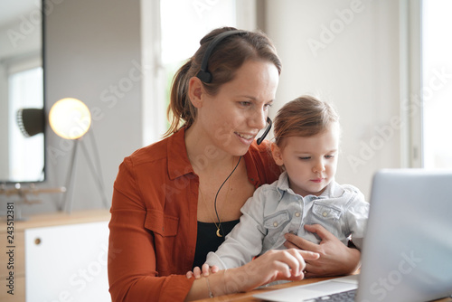 Obraz na plátně Mother working from home on computer with her young daughter