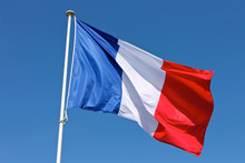 Flag Of France Waving Over A Blue Sky