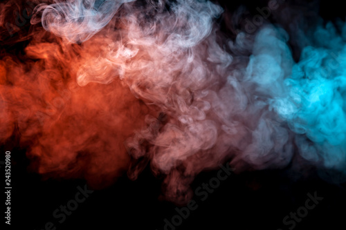 Clouds of isolated colored smoke: blue, red, orange, pink; scrolling on a black background in the dark close up. - 243520980