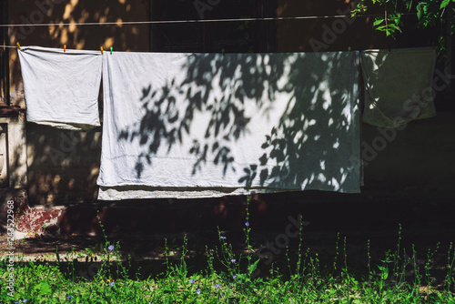 Fotografie, Obraz  Bedding hanging on rope with clothespins in sunny day