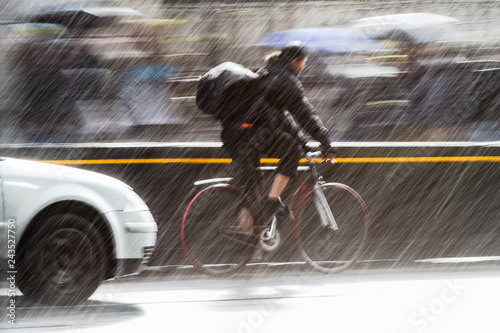 cyclist on a city street at heavy rain