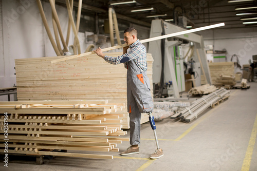 Photo  Disabled young man with an artificial leg is working at the furniture  factory
