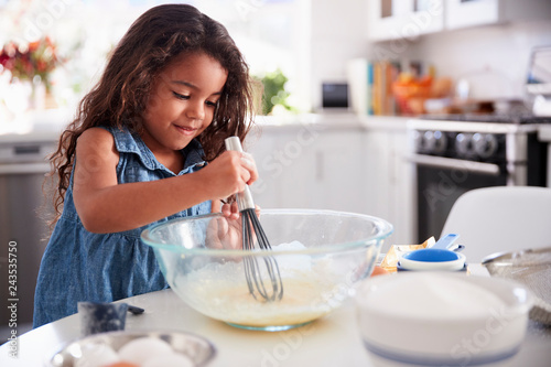 Fototapeta  Young Hispanic girl making a cake in the kitchen on her own, close up