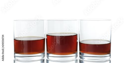 Glasses of scotch whiskey on white background