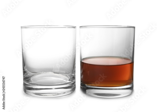 Empty and full whiskey glasses on white background