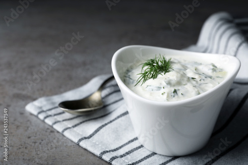 Cucumber sauce in ceramic bowl and spoon on grey background, space for text. Traditional Tzatziki
