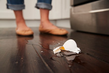 A Broken Egg On The Kitchen Floor After A Small Cooking Accident, Feet In The Background, Low Angle