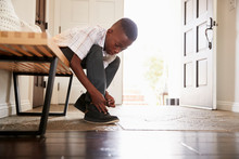 Low Angle View Pre-teen Black Boy Tying His Shoes Before Leaving Home, Selective Focus